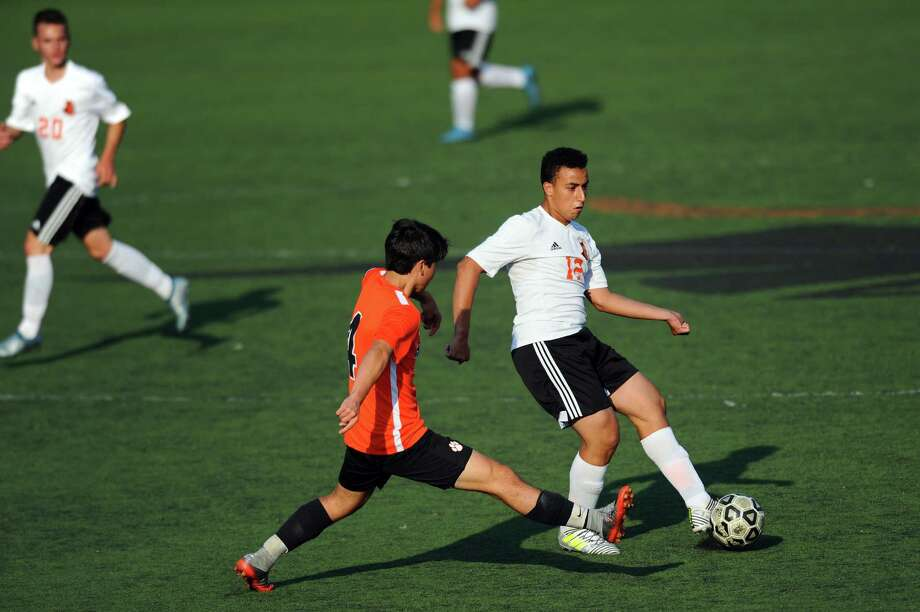 Stamford High School midfielder Mohammed Fagrouch keeps the ball away from Ridgefield High School defender Benjamin Caset Sasse during the varsity boys soccer game at Stamford High School in Stamford, Conn. on Monday, Sept. 11, 2017. Photo: Michael Cummo, Hearst Connecticut Media / Stamford Advocate