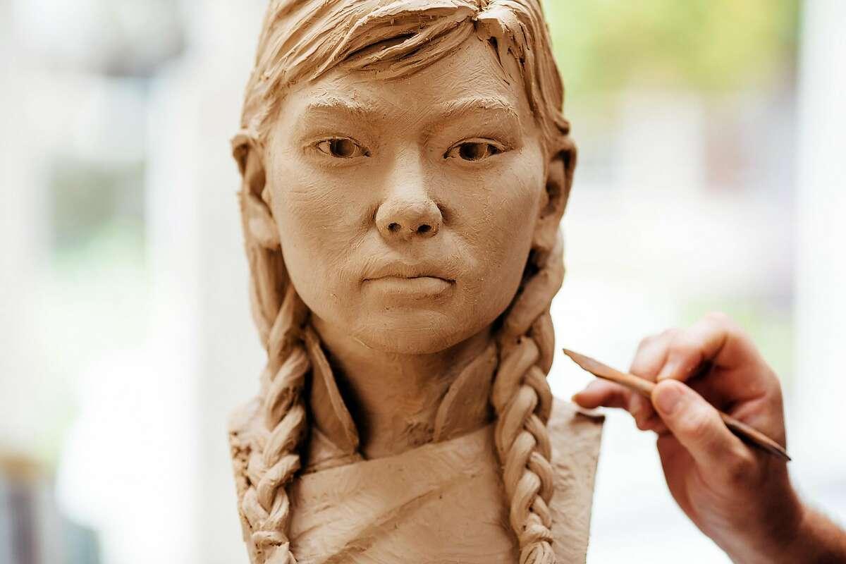 Sculptor Steven Whyte works on the face of one of the girls in the 'Women�s Column of Strength' memorial in his studio in Carmel, Calif. Friday, September 8, 2017.