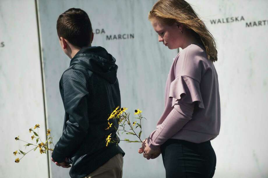 Everett Lata, left, 13, and his sister Ellie, right, 12, of Saylorsburg, Pa., place flowers by the name of their great-grandmother, Hilda Marcin, along the Wall of Names on Monday at the Flight 93 National Memorial in Shanksville, Pa. Photo: Stephanie Strasburg, MBI / Pittsburgh Post-Gazette