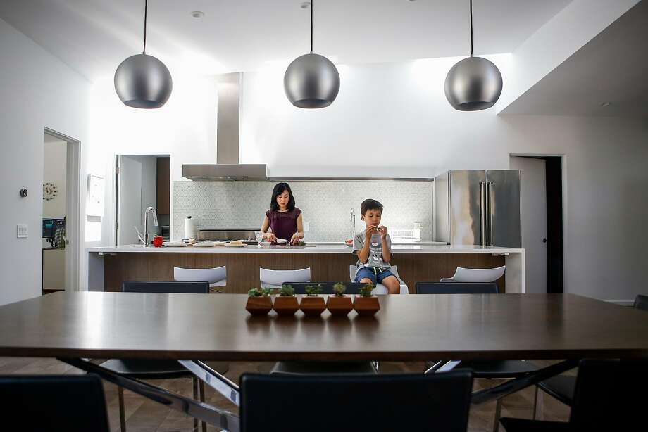 Susan Wang makes bread while her son Julien, 7, has a snack in the kitchen of their remodeled home in San Carlos. Photo: Nicole Boliaux, The Chronicle