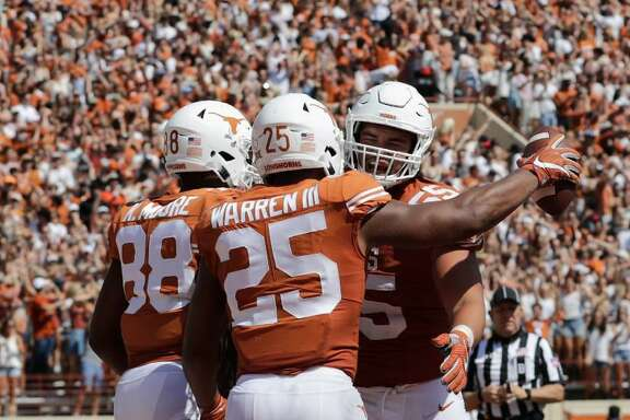 Connor Williams #55 of the Texas Longhorns congratulates Chris Warren III #25 after a touchdown in the second quarter at Darrell K Royal-Texas Memorial Stadium on September 9, 2017 in Austin, Texas.