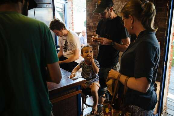 Ethan Gicker, center, of Nevada City, watches as his two-year-old son, Soren Gicker gobbles down his donut at Foxhound in Nevada City, Calif. Tuesday, September 5, 2017.