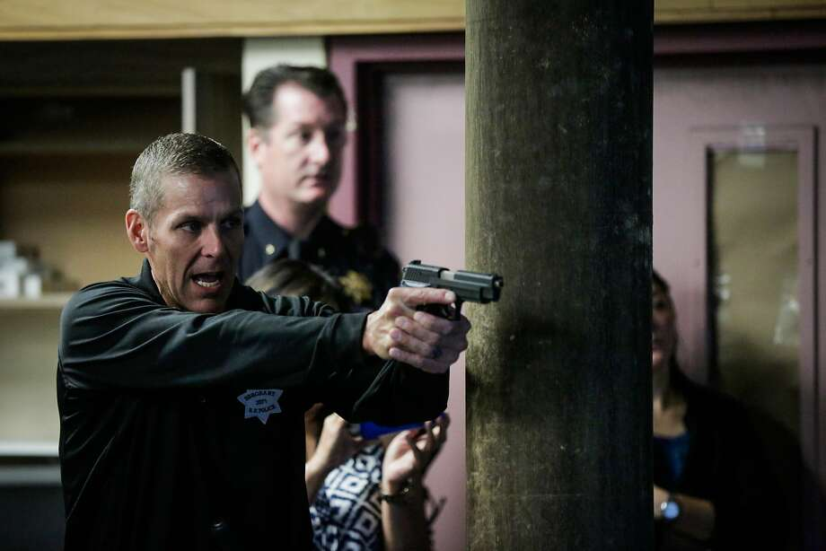 Sgt. Steven Pomatto (left) points a gun while simulating a scenario during a demonstration to the media on how police officers are trained to use force in San Francisco on Monday, Sept. 11, 2017. Photo: Gabrielle Lurie, The Chronicle