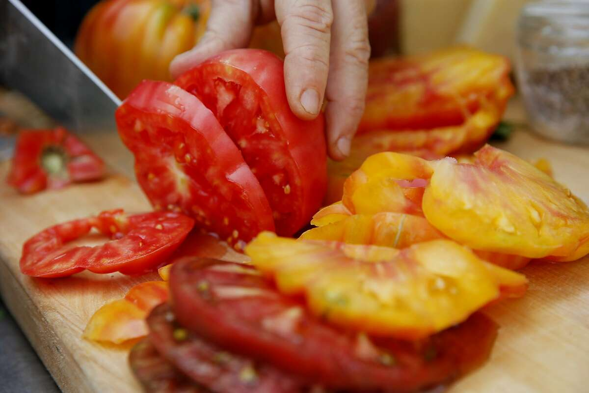 Kendra Kolling slices Soda Rock Farms tomatoes for her The Works sandwich at The Barlow on Tuesday, Aug. 22, 2017, in Sebastopol, Calif.
