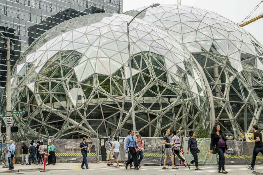 Pedestrians walk past a recently built trio of geodesic domes that are part of the Seattle headquarters for Amazon, Sept. 7, 2017. The online retail giant said it was searching for a second headquarters in North America in 2017, a huge new development that would cost as much as $5 billion to build and run, and house as many as 50,000 employees. Photo: Stuart Isett / The New York Times / NYTNS