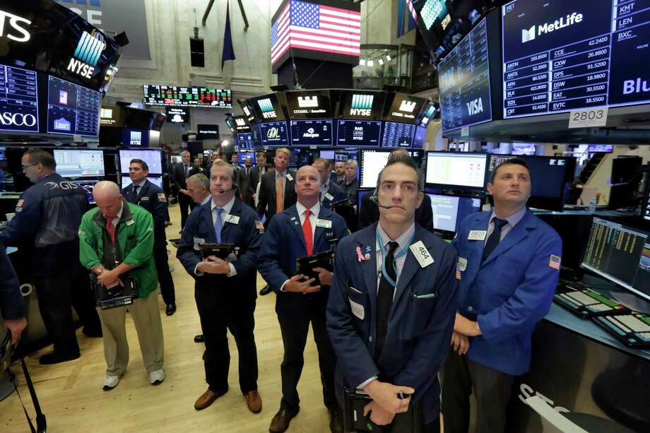 Traders on the floor of the New York Stock Exchange pause Monday for a moment of silence on the 16th anniversary of the Sept. 11 attacks. Photo: Richard Drew, STF / AP