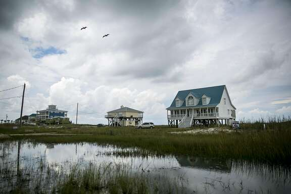 Houses sit along the flood zone in Dauphin Island, Alabama, U.S., on Wednesday, June 28, 2017. About 400 miles east of Houston, Dauphin Island was spared the initial impact of Hurricane Harvey. Yet this tiny sliver of land near the mouth of Mobile Bay is just as important as the battered metropolis to the debate over American disaster policy. Photographer: Nicole Craine/Bloomberg