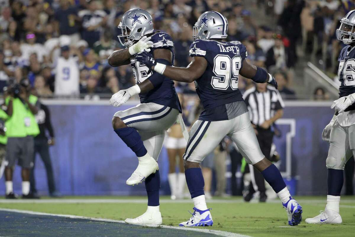Dallas Cowboys defensive end Lenny Jones (56) celebrates a sack with teammate defensive end Charles Tapper (99) during the second half of a preseason NFL football game against the Los Angeles Rams Saturday, Aug. 12, 2017, in Los Angeles.