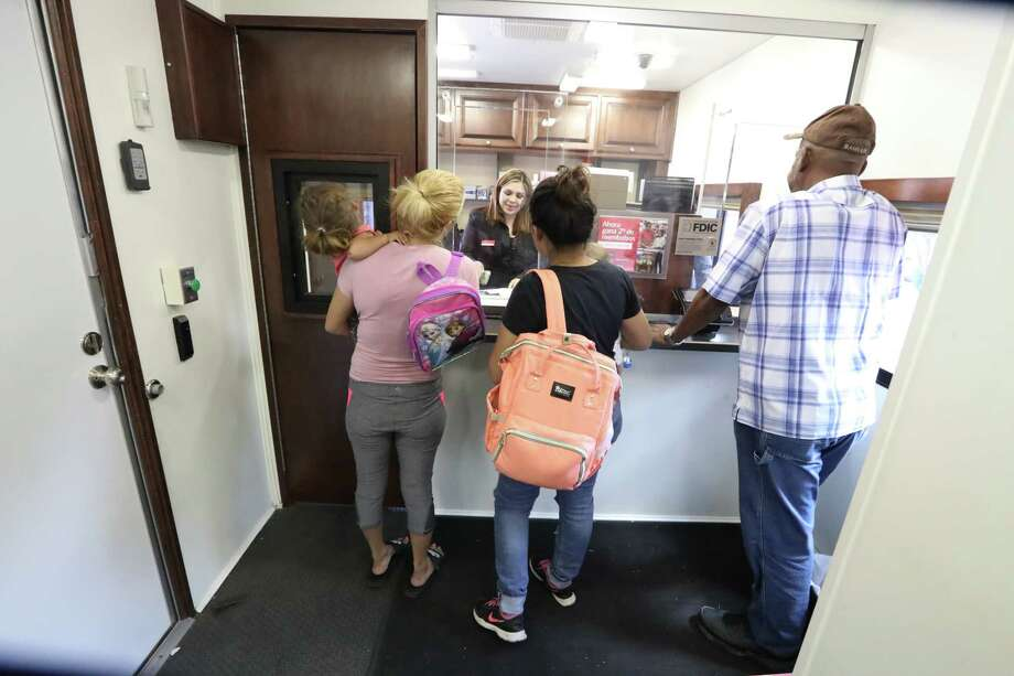 Customers use Bank of America's mobile financial center outside a flood-damaged branch office in east Houston. Photo: Steve Gonzales, Houston Chronicle / © 2017 Houston Chronicle