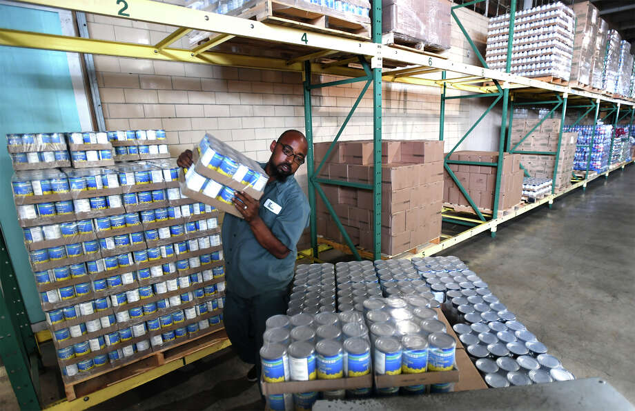 Jamal Holmes stacks cans at the Southeast Texas Food Bank on Monday. Following the damage of Hurricane Harvey to the area, the Hearst Corporation, the Beaumont Enterprise's parent company, donated $200,000 to the organization and previously pledged $1 million to the Red Cross for Hurricane Harvey.  Photo taken Monday, September 11, 2017 Guiseppe Barranco/The Enterprise Photo: Guiseppe Barranco, Photo Editor / Guiseppe Barranco ©