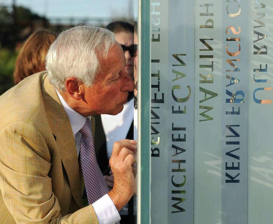 Ralph Sabbag, father of Jason Sabbag, who died in the 9/11 attacks, kisses his son's name on the September 11th Memorial during the September 11th Remembrance Service at Cos Cob Park in the Cos Cob section of Greenwich, Conn. Monday, Sept. 11, 2017. More than 200 people attended the ceremony on the 16-year anniversary of the 9/11 attacks on the World Trade Center. Names of the Greenwich residents lost in the attacks were read aloud, followed by a presentation of colors by the Greenwich Police and Boys & Girls Club of Greenwich honor guards and a rose-placing at the memorial. Photo: Tyler Sizemore / Hearst Connecticut Media / Greenwich Time