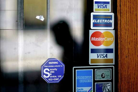 FILE - In this July 18, 2012, file photo, a pedestrian walks past credit card logos posted on a downtown storefront in Atlanta. On Monday, Sept. 11, 2017, Equifax said it has made changes to address customer complaints since it disclosed a week earlier that it exposed vital data on about 143 million Americans. Equifax has come under fire from members of Congress, state attorneys general, and people who are getting conflicting answers about whether their information was stolen. Equifax is trying again to clarify language about people's right to sue, and said Monday it has made changes to address customer complaints. (AP Photo/David Goldman, File)