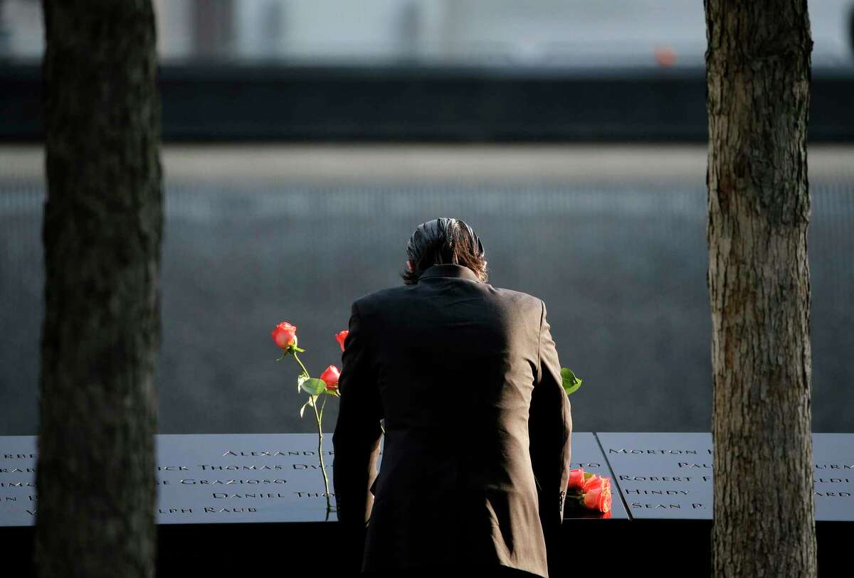 A man stands at the edge of a waterfall pool during a ceremony at ground zero in New York, Monday, Sept. 11, 2017. Holding photos and reading names of loved ones lost 16 years ago, 9/11 victims' relatives marked the anniversary of the attacks at ground zero with a solemn and personal ceremony. (AP Photo/Seth Wenig) ORG XMIT: NYSW106