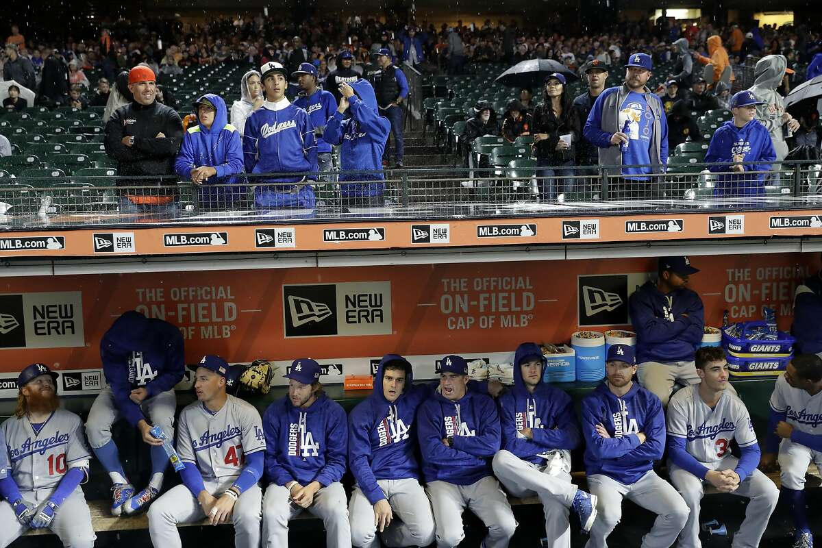 Los Angeles Dodgers players sit in the dugout during a rain delay during a baseball game against the San Francisco Giants Monday, Sept. 11, 2017, in San Francisco. (AP Photo/Marcio Jose Sanchez)