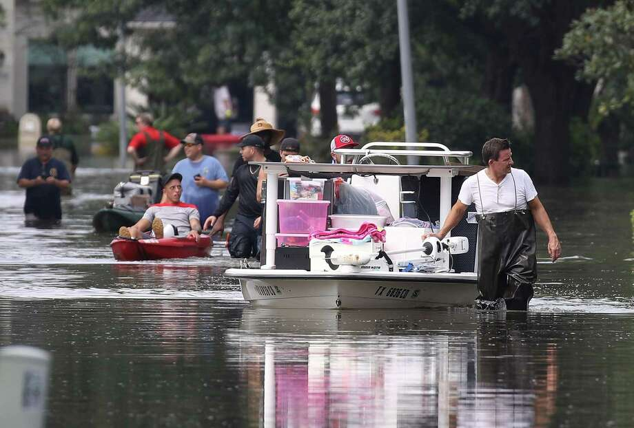 People use boats to help bring items out of homes in an area where a mandatory evacuation was under effect after flood water inundated them after torrential rains caused widespread flooding during Hurricane and Tropical Storm Harvey on September 3, 2017 in Houston, Texas. Harvey, made landfall near Rockport on August 25. Texas Attorney General Ken Paxton sued three businesses Tuesday for allegedly overcharging customers for fuel and hotel rooms in the wake of the massive storm system. Photo: Joe Raedle /Getty Images / 2017 Getty Images
