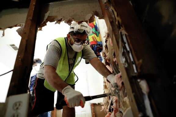 In this Sunday, Sept. 3, 2017, photo, volunteer Hashir Ayubi, of the the Ahmadiyya Muslim Youth Association helps clean out a flood-damaged home in Houston. Harvey that dumped an epic 52 inches of rain affected residents of all income levels. It's becoming apparent that the working poor who struggled before the storm will have an especially difficult time bouncing back. Those workers often don't get paid if they take time off to clean up and recover. (AP Photo/Gregory Bull)