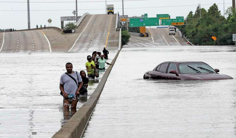 Evacuees wade down a flooded section of Loop 610 as floodwaters from Harvey rise on Sunday, Aug. 27, 2017. Photo: David J. Phillip, Associated Press / Copyright 2017 The Associated Press. All rights reserved.