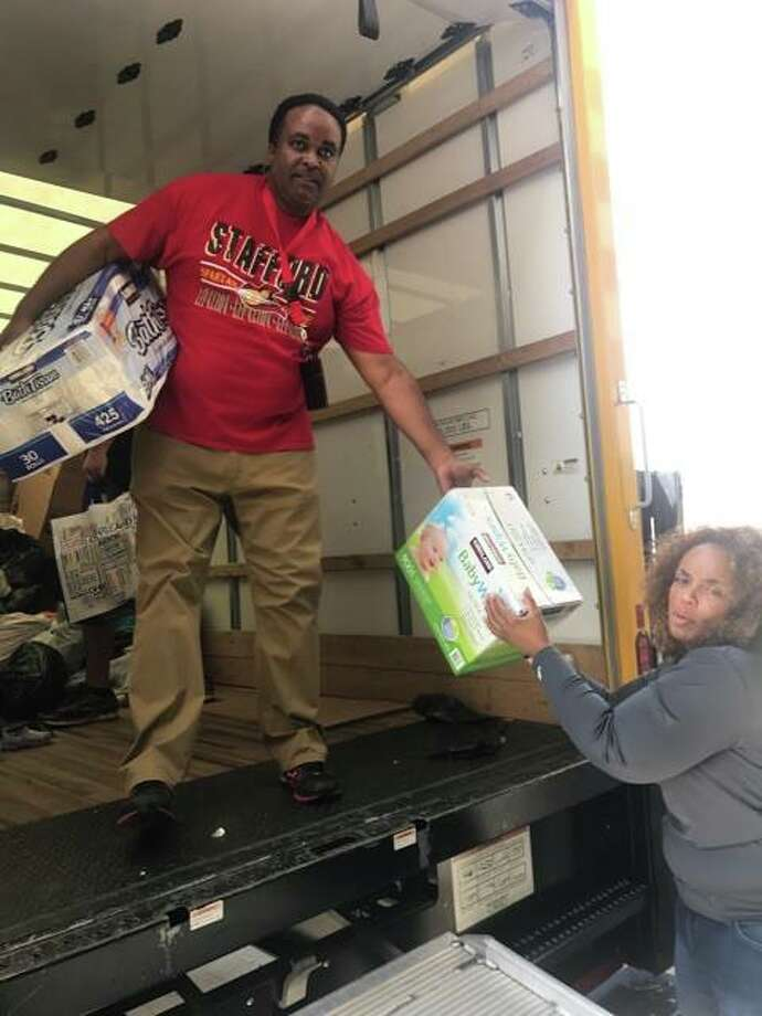 Stafford Municipal School District Superintendent Robert Bostic hands Hurricane Harvey donations from the Cleveland Browns to Stafford High Principal Misti Morgan Photo: Stafford MSD