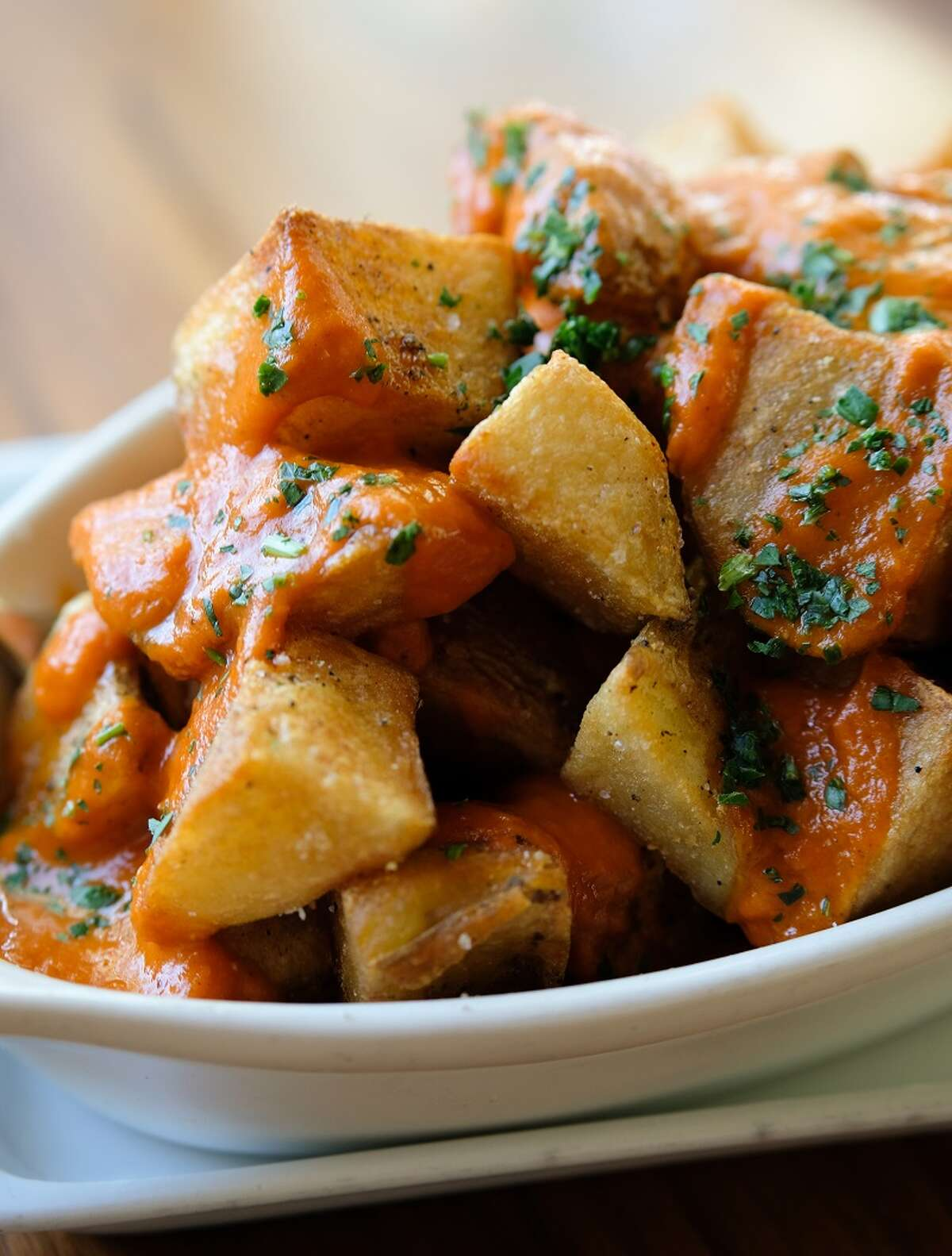 The new fall/winter menu at Bistro Menil was inspired by chef Greg Martin's recent trips to Spain. There are also new additions of Spanish wine to the wine list. Shown: Patatas bravas, an iconic Spanish dish.