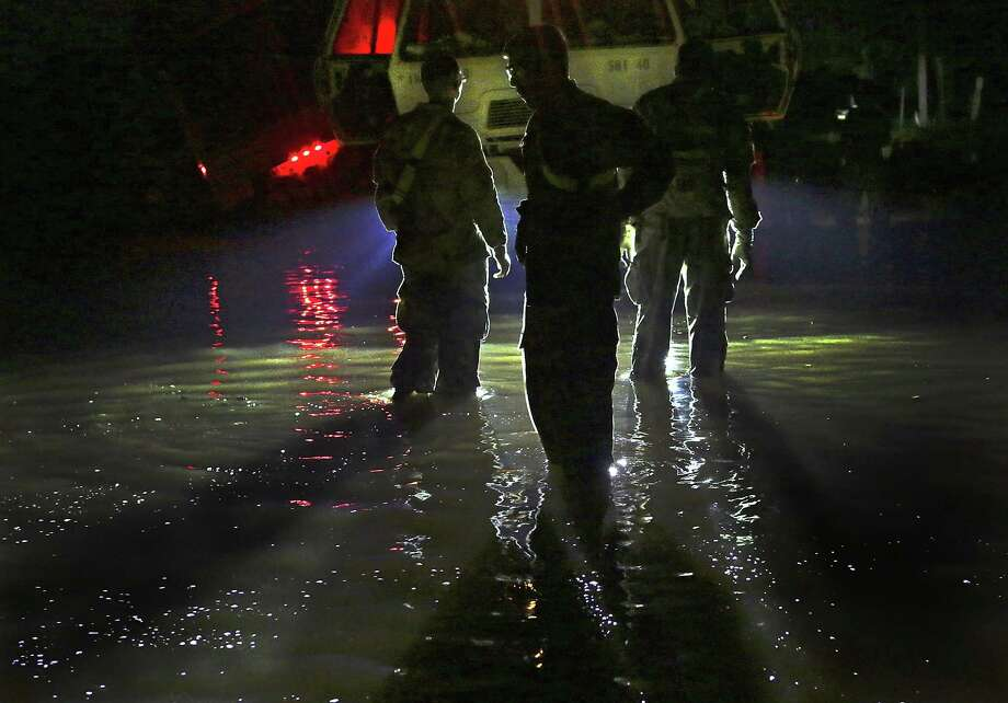 Members of the 49th Transportation Battalion and 1ST Medical Brigade wait in flood waters after one of their vehicles slide off the road during a search and rescue mission in Wharton, Tx on Friday, Sept. 1, 2017.  The team was able to pull the vehicle out with another of their vehicles. There were no injuries. Photo: Bob Owen, Staff / San Antonio Express-News / ©2017 San Antonio Express-News
