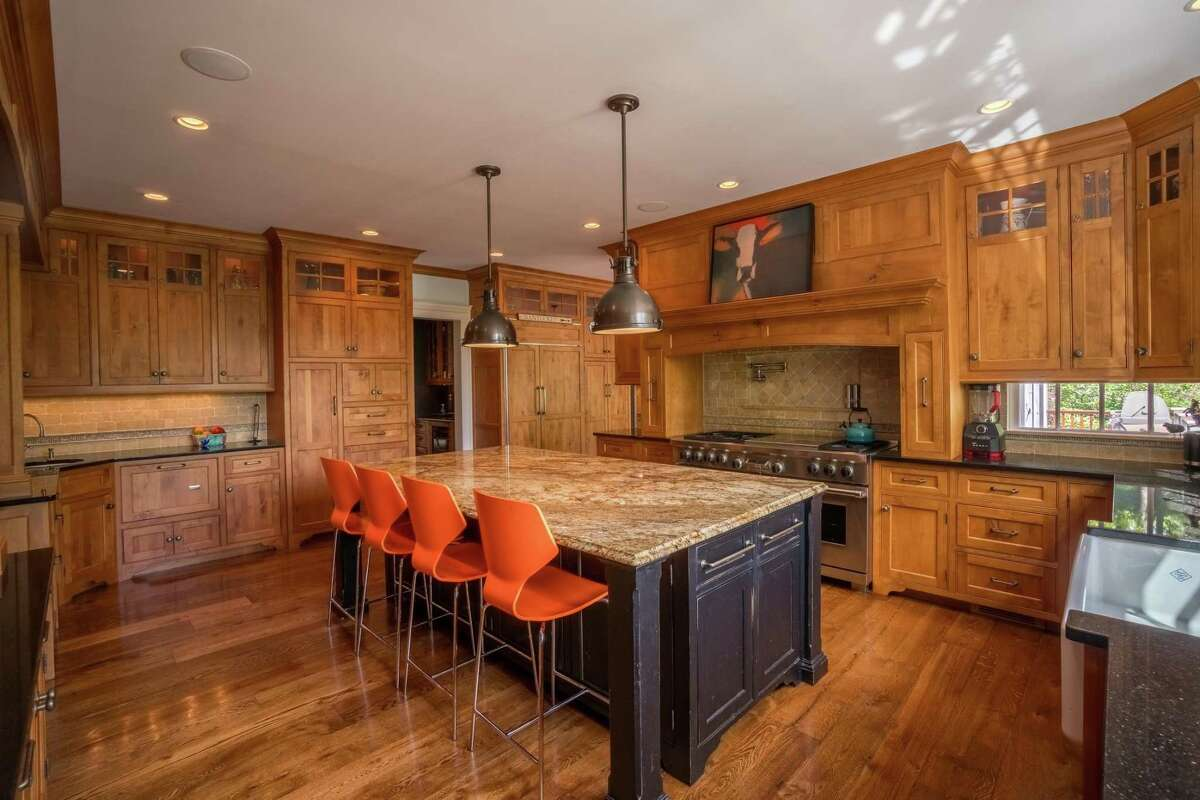 The kitchen has a Miele dishwasher and two Miele dishwasher drawers, double ovens alder wood cabinetry and a large center island.