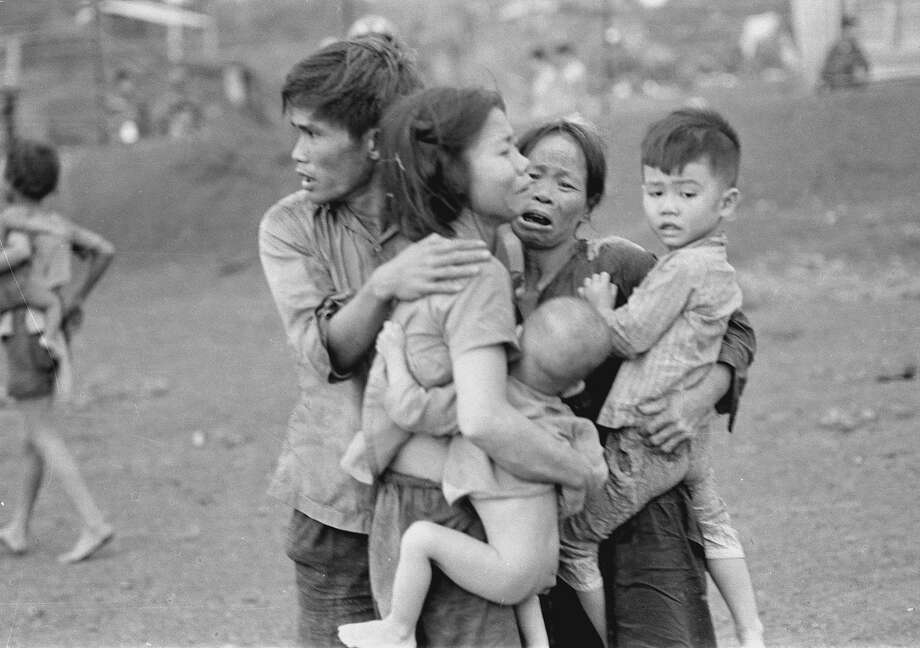 Civilians huddle together in Dong Xoai after an attack by South Vietnamese forces in June 1965. Photo: Courtesy AP/Horst Faas