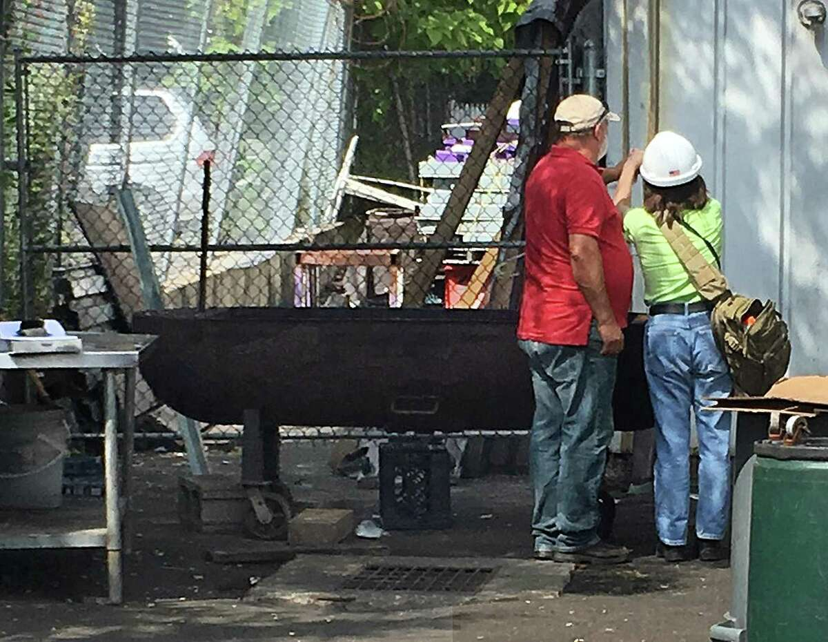 Marianne Bonito, right, a safety specialist with OSHA, and Tino Rodrigues, president of the Casa Do Benfica soccer club on federal road, inspect the grill that board member David Mendez became impaled on Tuesday after falling from the roof.