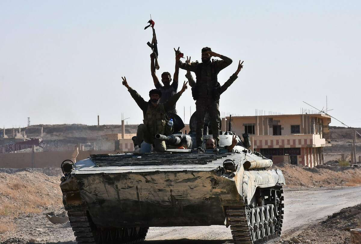 Syrian government forces celebrate in the eastern Syrian city of Deir Ezzor on September 11, 2017 as they continue to press forward with Russian air cover in the offensive against Islamic State group jihadists across the province. Syrian army reinforcements arrived in Deir Ezzor for a new push against the Islamic State group, as a second day of suspected Russian strikes killed 19 civilians in the area. / AFP PHOTO / George OURFALIANGEORGE OURFALIAN/AFP/Getty Images