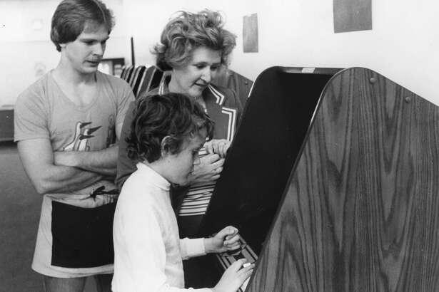 Rick Enszer, left, and Jill and Jon Tessin at The Corridor arcade. June 1982