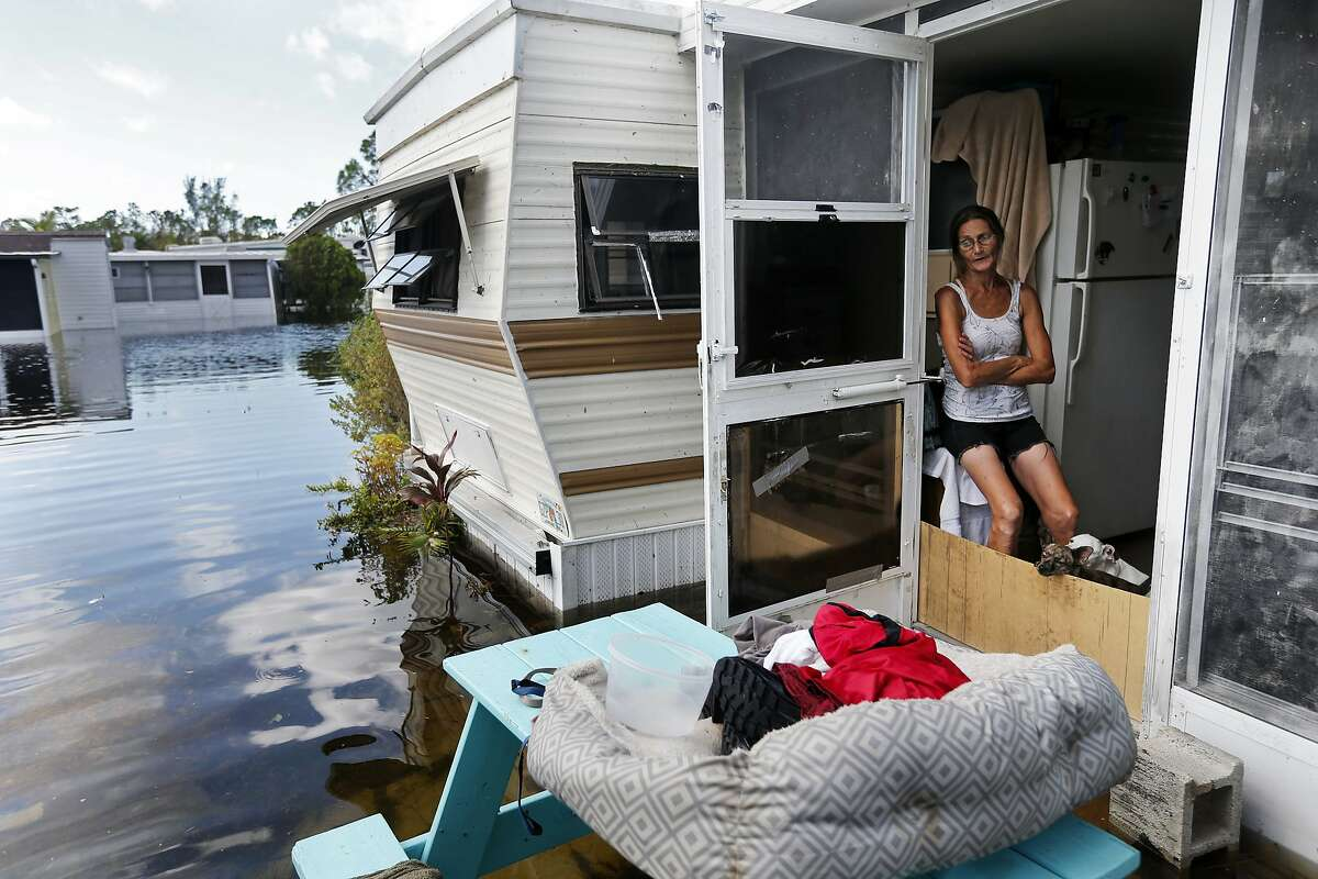 Cherie Ethier sits in her mobile home with her pets surrounded by floodwater, in the Marco Naples RV Resort in the aftermath of Hurricane Irma, in Naples, Fla., Tuesday, Sept. 12, 2017. (AP Photo/Gerald Herbert)