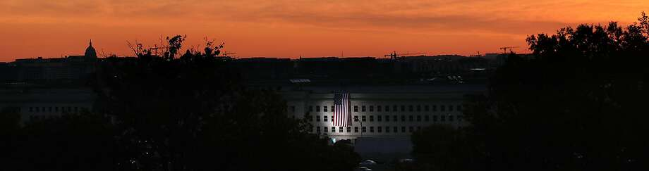 As the U.S. Capitol is seen in the background, an American flag is unfurled on the side of the Pentagon to commemorate the anniversary of the 9/11 terror attacks. Photo: Alex Wong, Getty Images