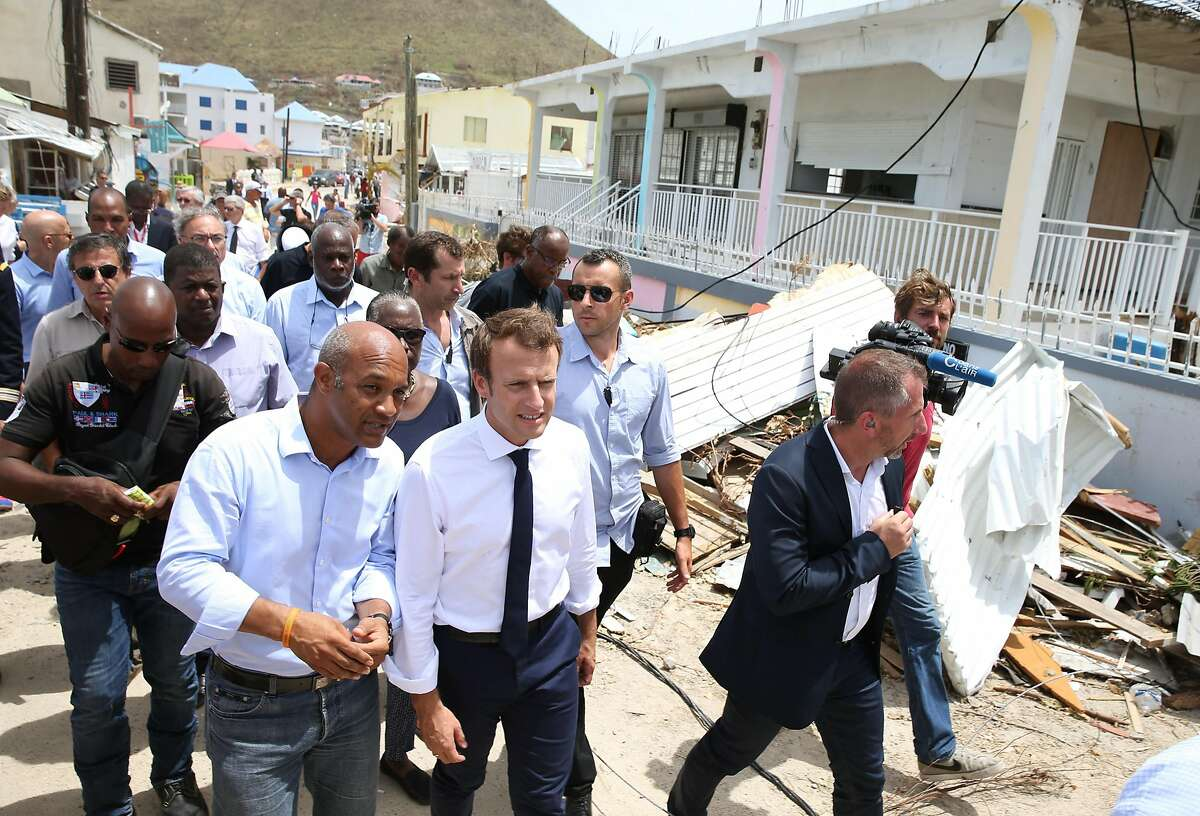 GRAND CASE, SAINT MARTIN - SEPTEMBER 12: Emmanuel Macron (C), President of France, witn Saint Maarten President Daniel Gibbs (L) during his visit after the passing of Hurricane Irma on September 12, 2017 in Grand Case, Saint Martin. The Caribbean island sustained extensive damage.(Photo by Jose Jimenez/Getty Images)