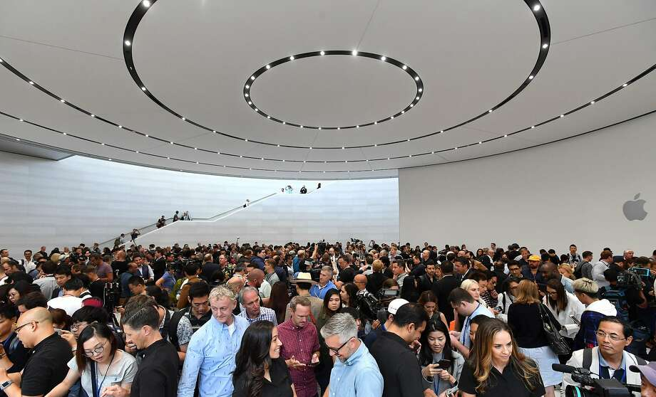 Above: attendees try out new Apple products during a media event at Apple's new headquarters in Cupertino. At left: Apple CEO Tim Cook (right) shows off the new iPhone X at the event. Photo: JOSH EDELSON, AFP/Getty Images