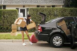 Young woman putting cardboard boxes in car trunk, side view