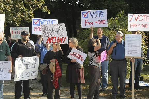 "Protesters gather on Tuesday, Sept. 12, 2017, at Saint Anselm College in Manchester, N.H., ahead of a day-long meeting of the Trump administration's election integrity commission. They argue the commission, which is tasked with investigating voter fraud, is a sham. Signs reading ""Vote Free or Die"" played off New Hampshire's motto: ""Live Free or Die."" (AP Photo/Holly Ramer)"