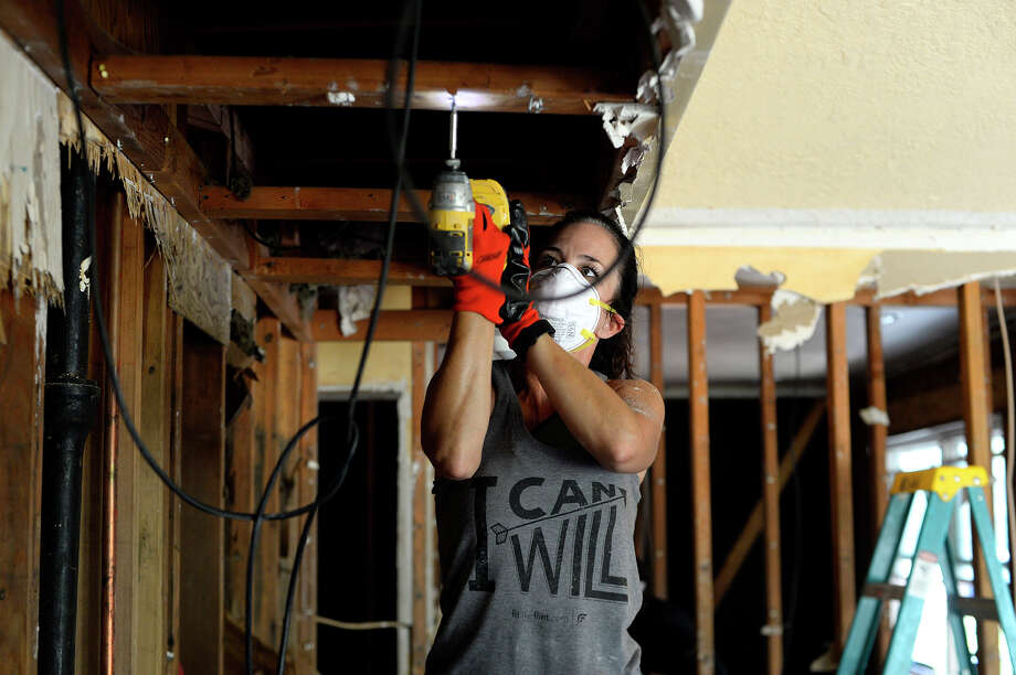 Kelly McGlaun removes drywall screws from studs at her home in Pinewood Estates on Tuesday. McGlaun was on vacation in Mexico when Harvey hit, adding to her stress not knowing how her house had fared.  Photo taken Tuesday 9/12/17 Ryan Pelham/The Enterprise Photo: Ryan Pelham / ©2017 The Beaumont Enterprise/Ryan Pelham