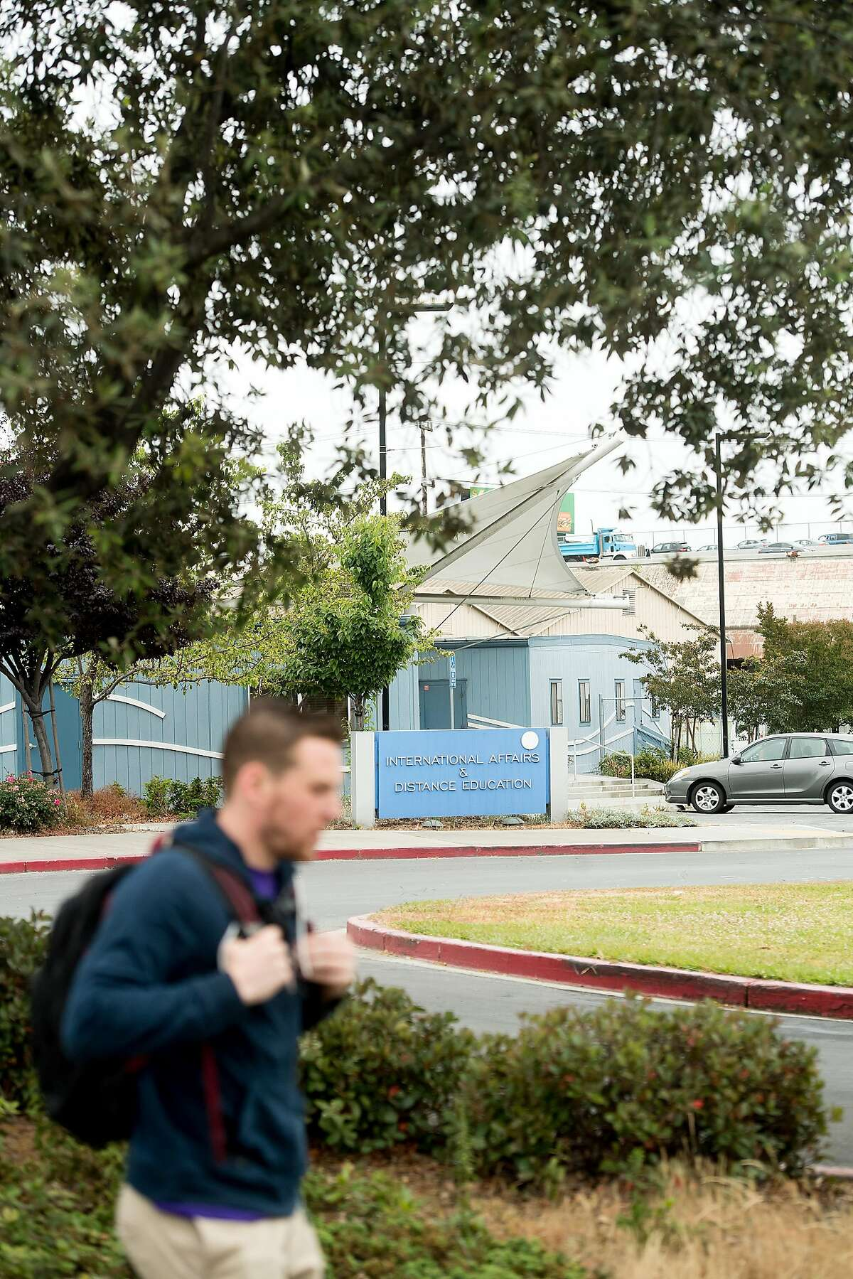 A pedestrian passes a building at the Peralta Community College District offices, one of the sites under consideration for a new Oakland Athletics baseball stadium, on Tuesday, May 30, 2017, in Oakland, Calif.