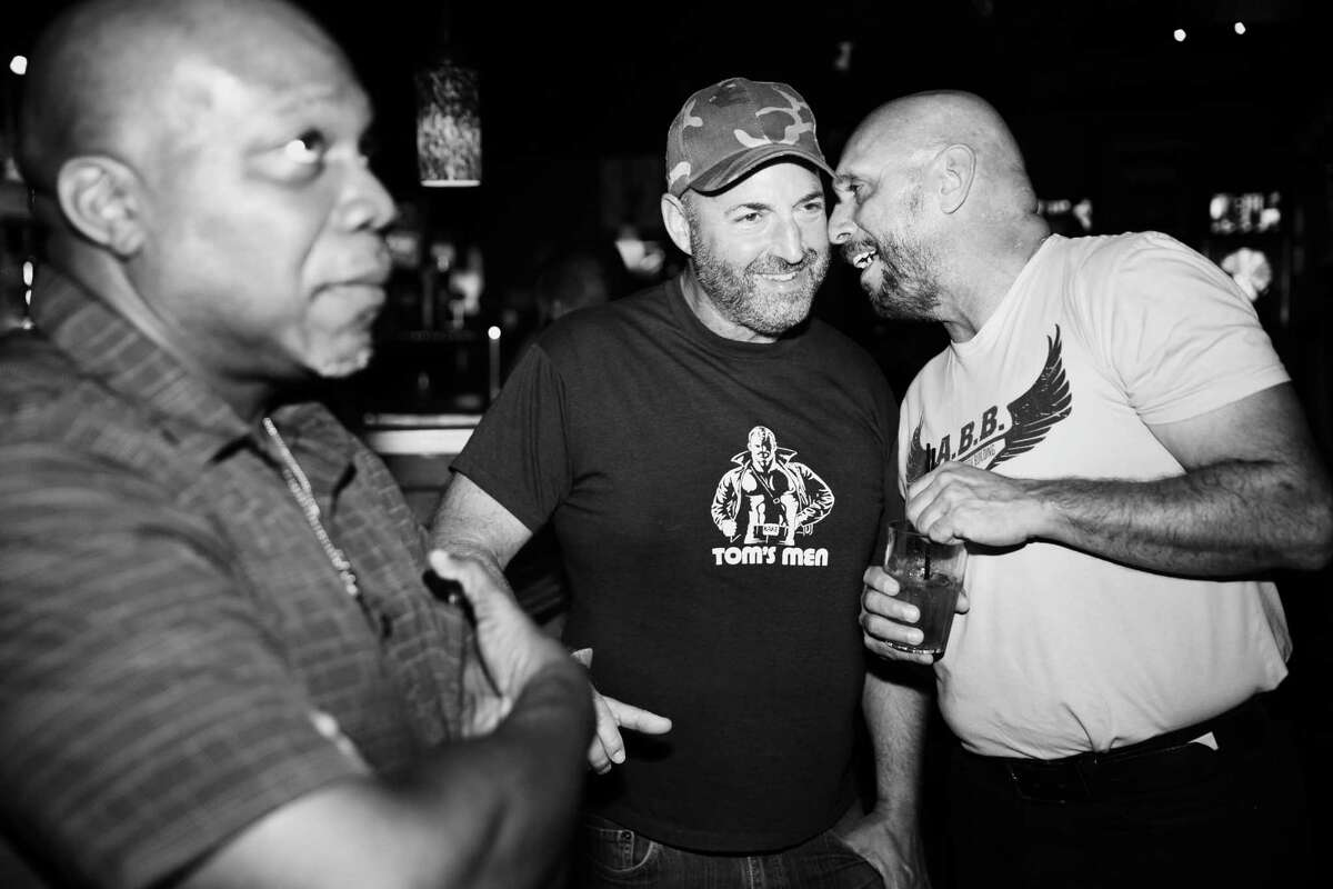 Mike Walhbrink, right, talks to his boyfriend Keith Klegman, center, as they hang out with Paul Brown, left, at C.C. Attle's. Walhbrink and Brown met in the Air Force 30 years ago and meet up with a group of old friends every year to reconnect. They planned to hit several area gay bars over the weekend. Photographed Saturday, Aug. 26, 2019.