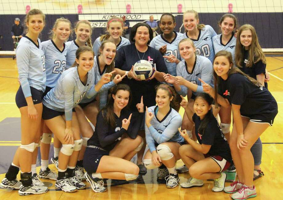 Kingwood High School varsity volleyball players pose around their head coach Ashley Earhart after their victory against Baytown Sterling High School, marking the 300th win of Earhart's coaching career Oct. 4 and Kingwood High School. Photo: Photo By Mike Janikula