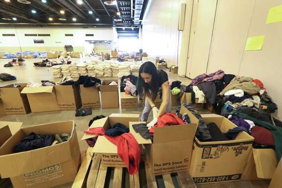 Rocio Gomez, BakerRipley, sorts clothes in the NRG Center shelter Tuesday, Sept. 12, 2017, in Houston.
