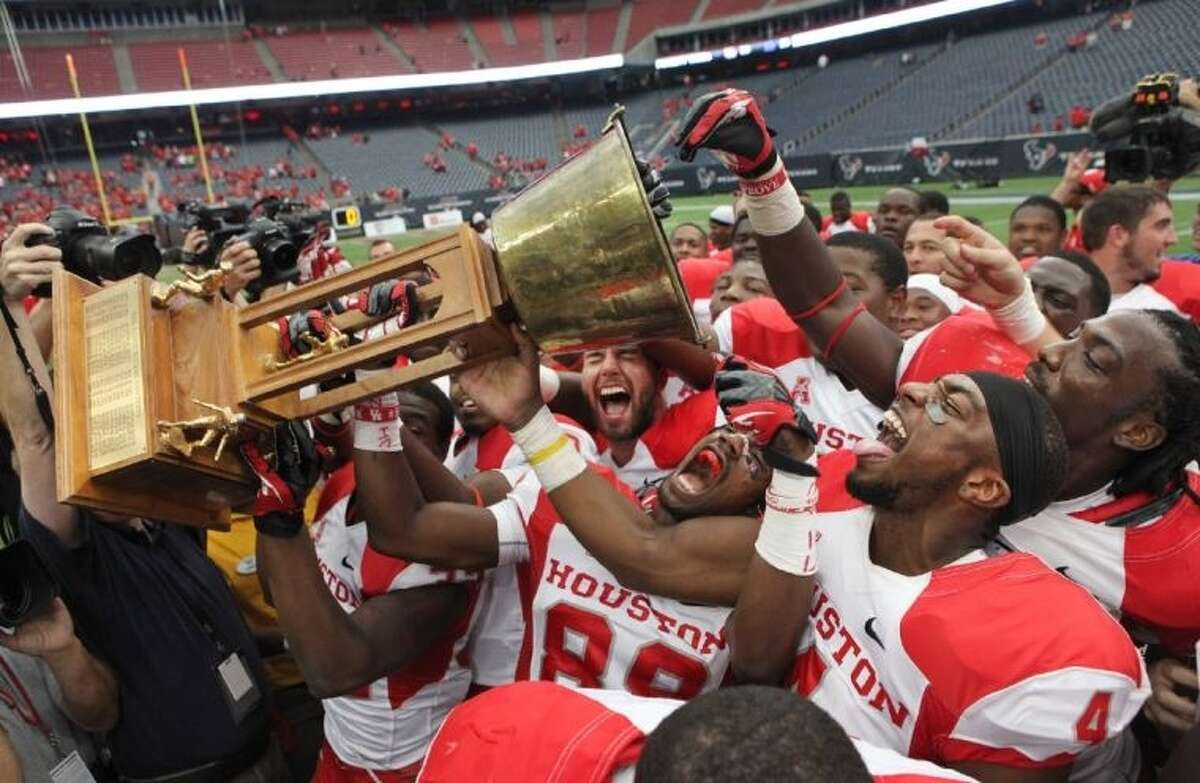 University of Houston players celebrate with the Bayou Bucket trophy after the Cougars defeated the Rice Owls 31-26 at Reliant Stadium.