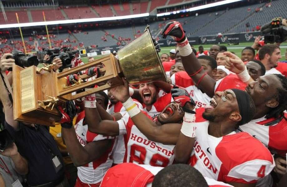 University of Houston players celebrate with the Bayou Bucket trophy after the Cougars defeated the Rice Owls 31-26 at Reliant Stadium. Photo: Alan Warren / Internal