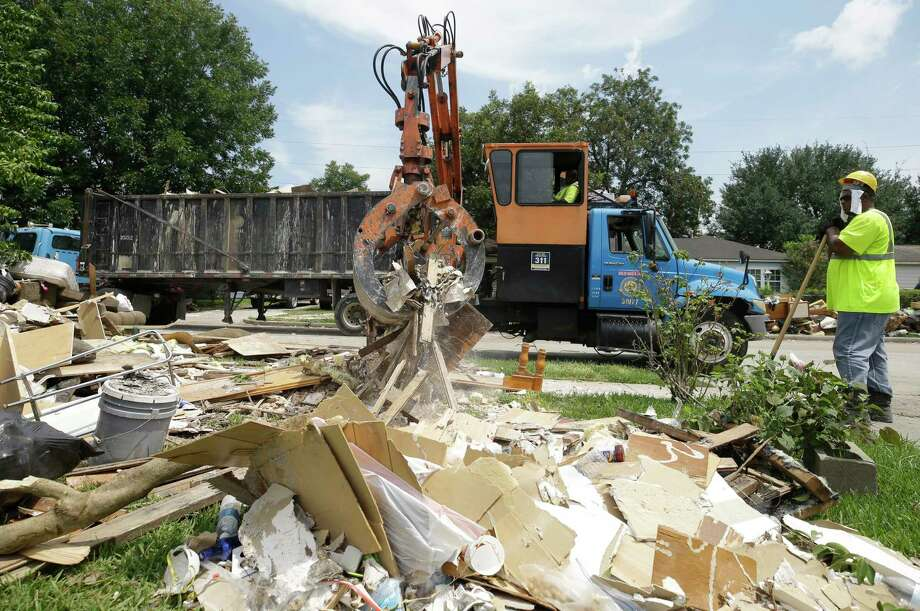 City of Houston crews work to remove debris along Terminal Street in Houston's Denver Harbor neighborhood last week.  Much of the area was flooded in the aftermath of Hurricane Harvey. ( Melissa Phillip / Houston Chronicle ) Photo: Melissa Phillip, Staff / © 2017 Houston Chronicle