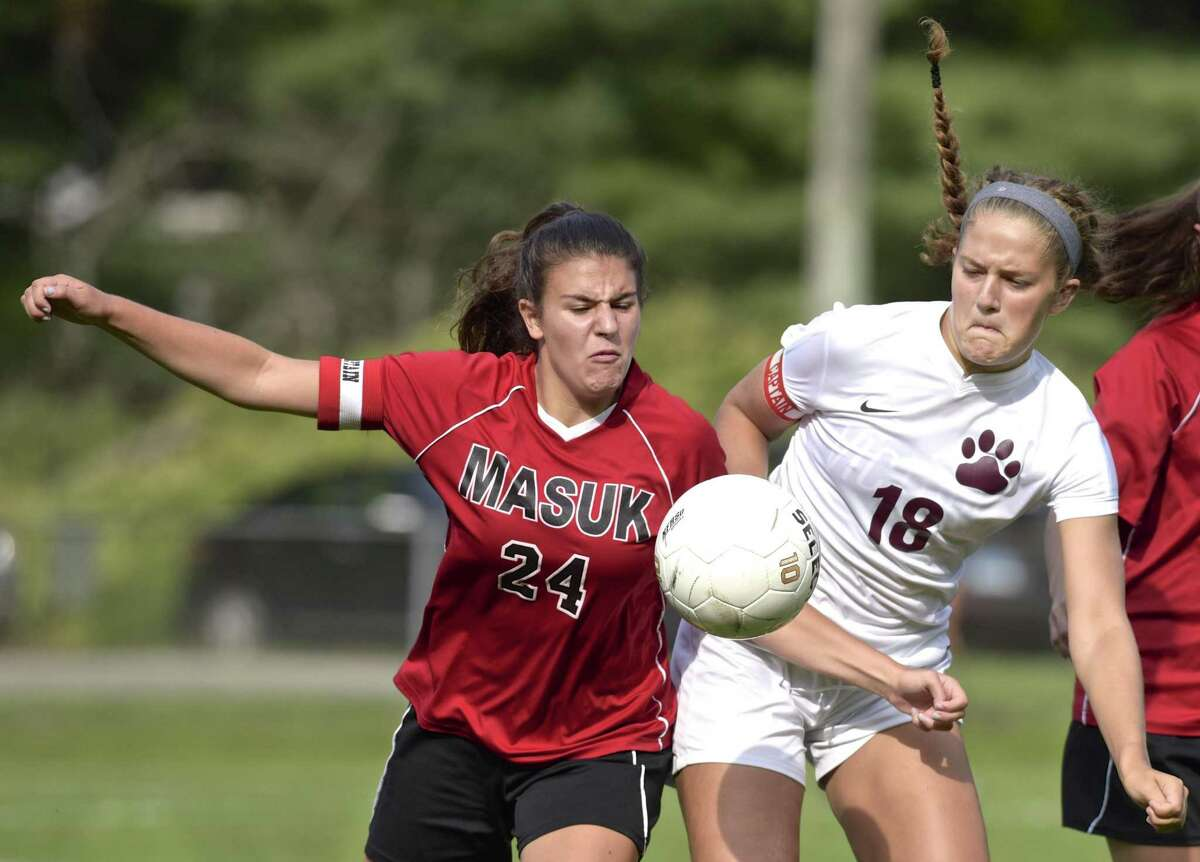 Masuk's Chloe Shawah (24) and bethel'sLily Daniels (18) fight for the ball in the girls soccer game between Masuk and Bethel high schools, Tuesday, September 12, 2017, at Rourke Field, in Bethel, Conn.