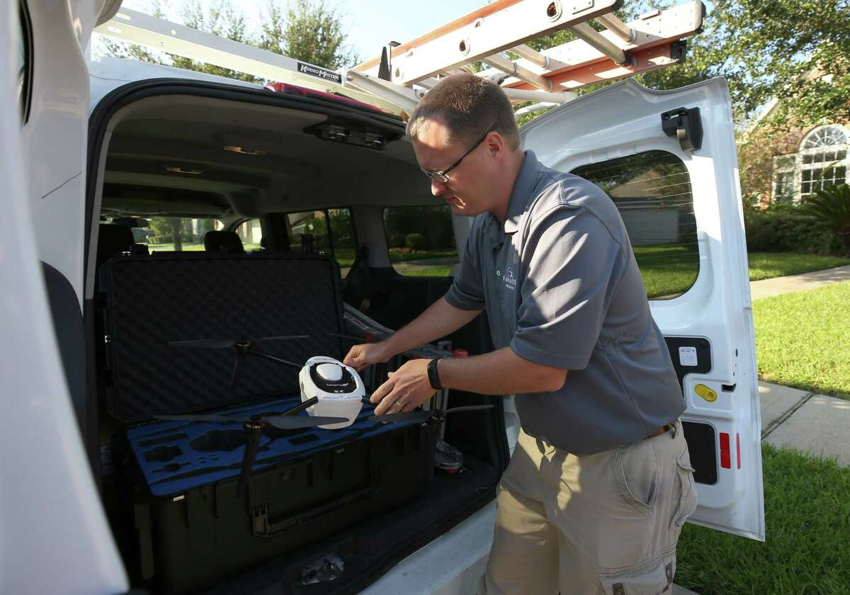 Brent Hazen, a property claims representative for Farmers Insurance, grabs a drone to examine the damage of a policy-holder on Ambrosia Springs Lane in Katy.