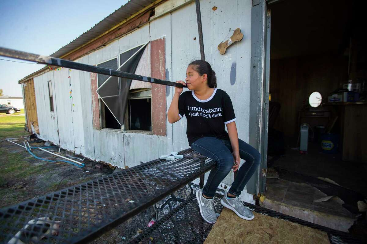 Jazmyn Oviedo, 10, sits on what was the front entrance to her family's home in Tivoli, TX, while her father salvages lumber to help fix another roof in the community, Tuesday, Sept. 12, 2017. Jazmyn and her family were not home when Hurricane Harvey hit, but when they returned home, they found their trailer and two additional relatives' trailers destroyed by the storm. Tivoli, an unincorporated town located between Port Lavaca and Rockport, was hit hard by Hurricane Harvey.