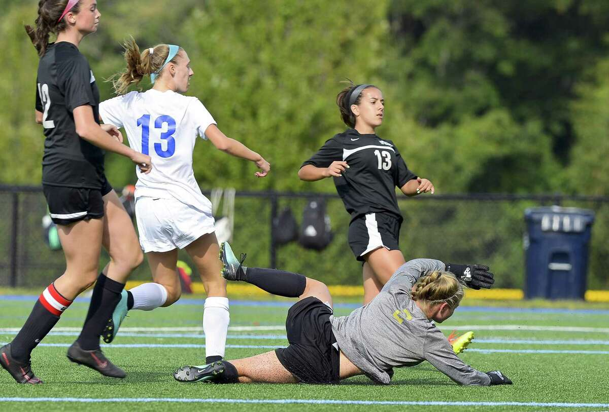 Darien Ellen Harnisch (13) follows her shot past Trumbull goalie Maryna Barone for a first half goal in a FCIAC varsity girls soccer game on Tuesday, Sept. 12, 2017 in Darein, Connecticut. Darien defeated Trumbull 1-0.