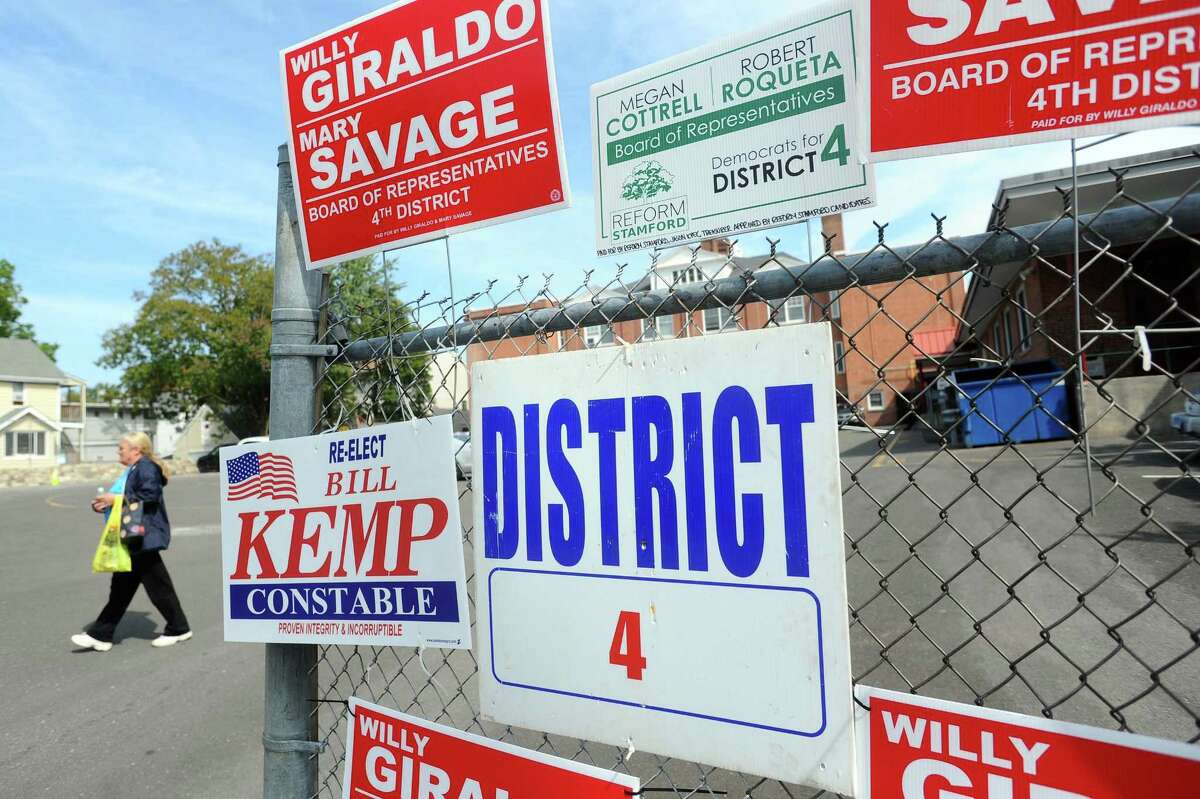 A woman walks out of the district 4 polling station at K.T. Murphy School and past political signs during the primary election in Stamford, Conn. on Tuesday, Sept. 12, 2017.