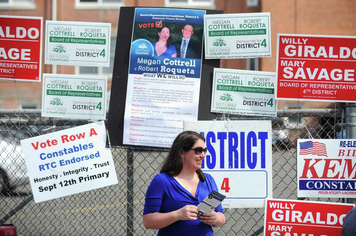 District 4 candidate Megan Cottrell smiles at a potential voter outside the polling station during the primary election at K.T. Murphy School in Stamford on Tuesday.