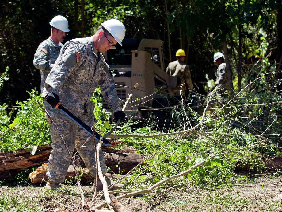 Private E-2 Joshua Meeks works to clear brush as 80 members of the National Guard work to clear out an area of land off FM 149 and Martin Luther King Jr. Drive which floods frequently, Friday in Montgomery. The work after Tropical Storm Harvey will serve to jump start the larger project as part of a General Land Office grant scheduled to be completed this winter. Photo: Jason Fochtman, Staff Photographer / © 2017 Houston Chronicle